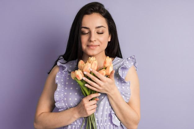 폴카 도트 드레스에 매력적인 갈색 머리는 보라색 벽에 봄 꽃을 보유