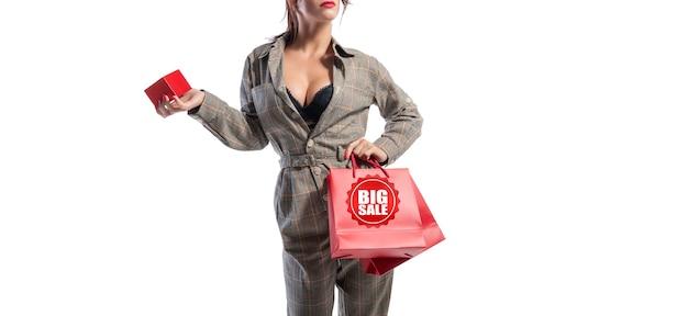 빨간 가방과 보석 상자를 들고 스튜디오에서 포즈를 취하는 안경을 쓴 매력적인 브루네트. 흰 바탕. 쇼핑 개념입니다. 혼합 매체