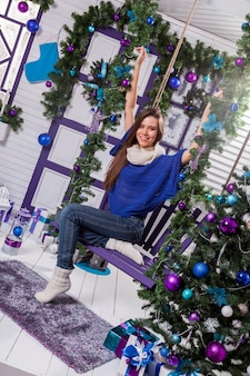 Charming brunette in jeans and a blue sweater sits on a swing in christmas