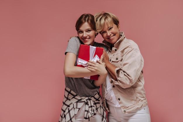 Очаровательная брюнетка дама в серой футболке и клетчатой рубашке держит красную подарочную коробку, улыбается и позирует со старой блондинкой на изолированном фоне.
