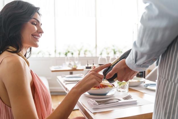 魅力的なブルネットの女性がラベルに触れて、カフェの労働者がアルコール飲料のボトルを保持している間笑顔