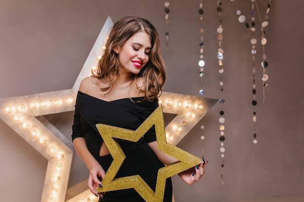 魅力的なブルネットは目をそらした。黒のエレガントなドレスで金の星とポーズをとる少女。