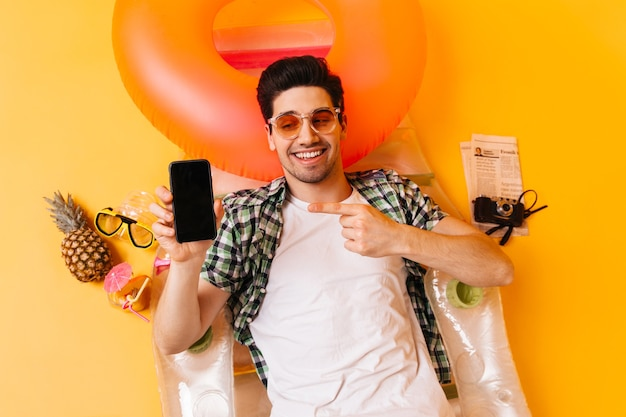 Charming brunette man in plaid shirt and orange glasses points to black smartphone. guy is resting on inflatable mattress.