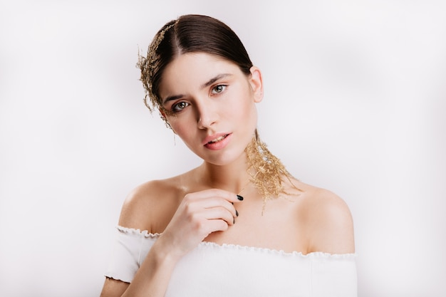 Очаровательная брюнетка чувственно на белой стене. девушка без макияжа в белом топе держит сухой лист.