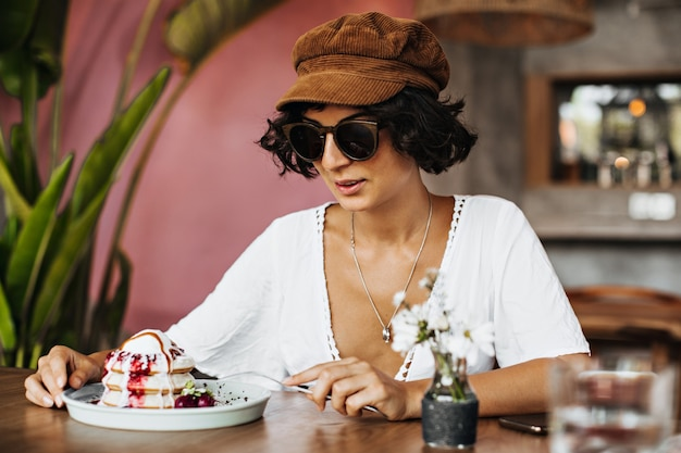 Charming brunette tanned woman in sunglasses and cap eats dessert in cafe