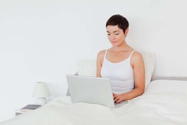Charming brunette using a laptop