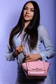 Очаровательная брюнетка с длинными волосами в джинсовой одежде держит розовую сумочку