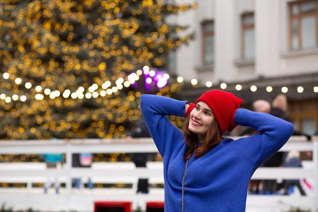 クリスマスフェアで楽しんでいる魅力的なブルネットの女性。テキスト用のスペース