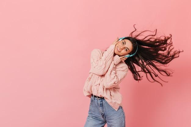 ピンクの背景で踊るヘッドフォンで魅力的なブルネットの女性。ジーンズとセーターでポーズをとる元気な女性。