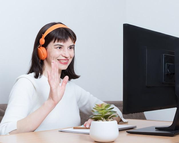 Очаровательная брюнетка в оранжевых наушниках с видеозвонком и приветственным жестом сидит за столом у себя дома перед монитором компьютера