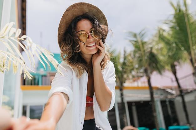 야자수와 함께 selfie를 만드는 흰 셔츠에 매력적인 갈색 머리 여자.