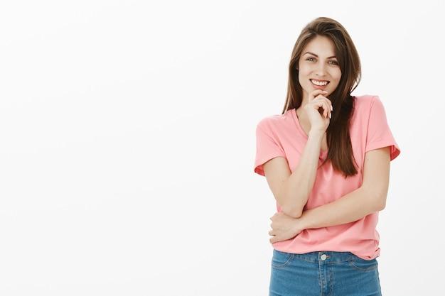 Очаровательная брюнетка женщина позирует в студии