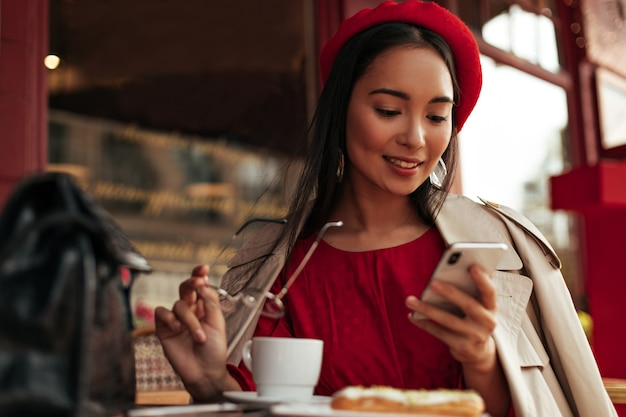 Charming brunette woman in red beret, dress and beige trench coat smiles, holds eyeglasses and relaxes in street cafe