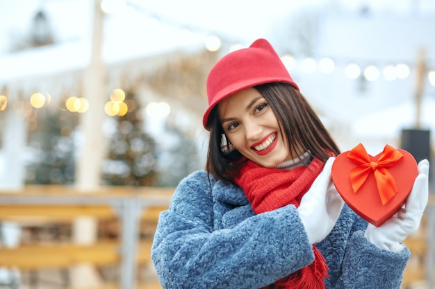 Charming brunette woman in winter coat holding a gift box at christmas fair. space for text
