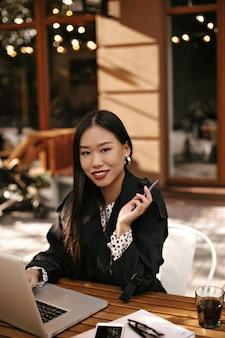 Affascinante donna bruna con labbra luminose sorride ampiamente e tiene la penna