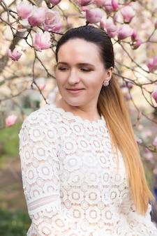 裸のメイクで魅力的なブルネットの女性、レースのブラウスを着て、咲くモクレンの花の近くでポーズをとる