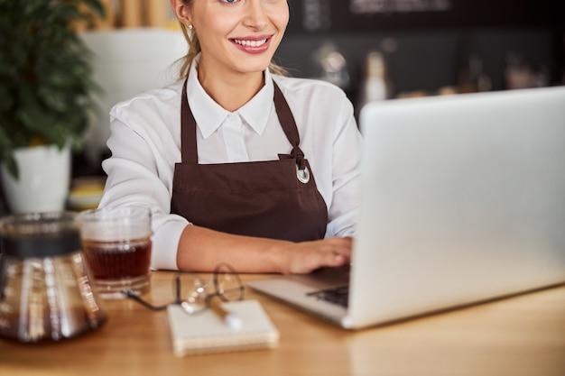 노트북을 사용하는 동안 나무 책상에서 시간을 보내는 매력적인 비즈니스 여성