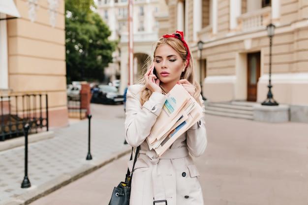 エレガントなメイクとブロンドの髪を持つ魅力的なビジネスレディが仕事に急いでいます。新聞を保持し、電話で話しているベージュのコートを着た若い女性の屋外の肖像画。