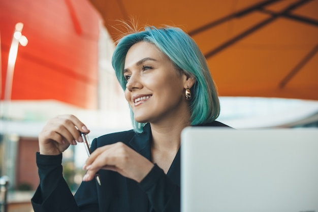 파란 머리가 레스토랑에 앉아 컴퓨터로 작업하는 매력적인 비즈니스 우먼