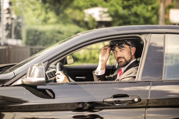 Charming businessman in his car