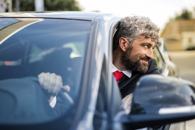 Charming businessman in his car
