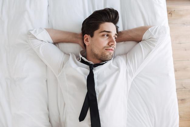 호텔 아파트에서 침대에 누워 공식적인 옷을 입고 매력적인 사업가