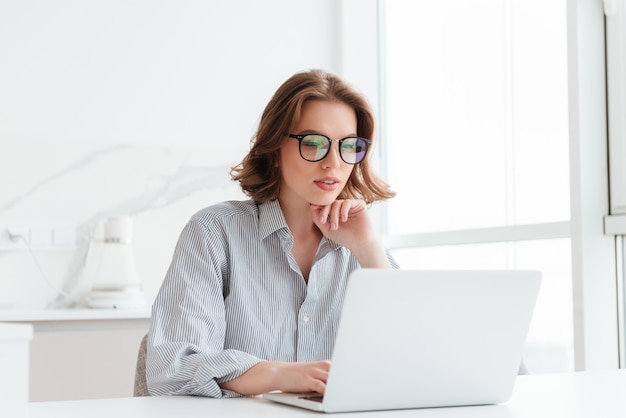 Charming businesswoman in glasses and striped shirt working with laptop computer while siting at home