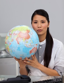 Charming businesswoman holding a globe
