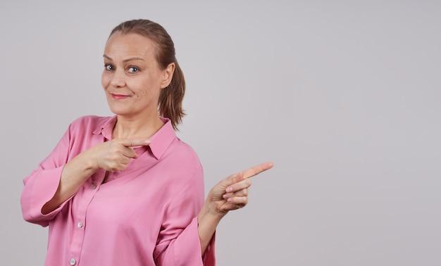 灰色の背景にポーズをとって、カメラを見て、横に指を指している魅力的な実業家。テキスト用のスペースをコピーします。