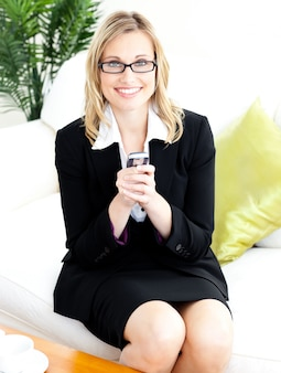 Charming businesswoman sending a text sitting on the sofa