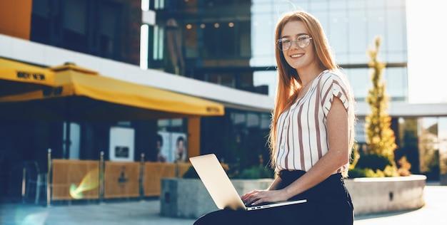 Очаровательная бизнесвумен в очках и рыжих волосах позирует снаружи с ноутбуком, сидя на скамейке