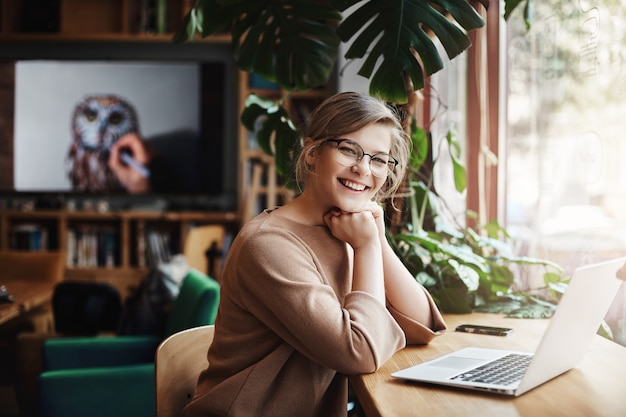 Charming and carefree european female with fair hair in glasses, sitting near window and laptop, leaning on hands.