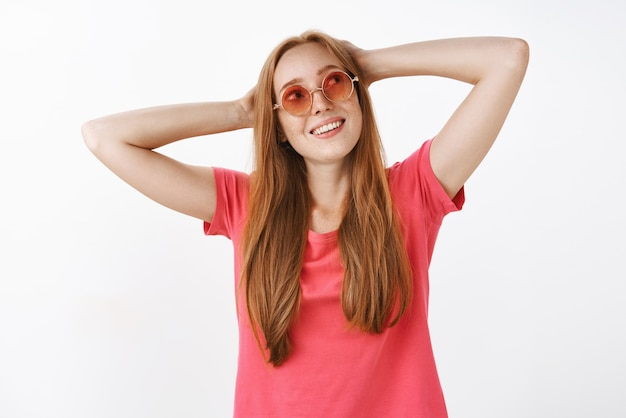 Charming carefree hippie girl with ginger hair and freckles in stylish pink sunglasses holding hands behind head standing in lazy pose and gazing at upper right corner