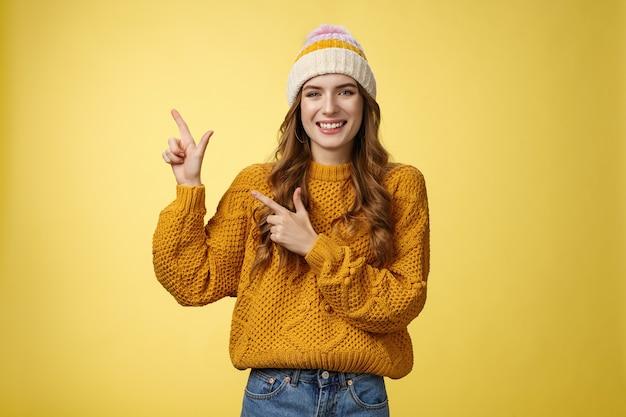Affascinante spensierata sorridente giovane 20s donna che indossa un cappello maglione che punta l'angolo in alto a sinistra lateralmente condividendo un link interessante promozione fantastica felice di consigliare un prodotto fresco, sfondo giallo