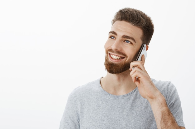 Affascinante giovane imprenditore di successo spensierato con gli occhi azzurri e la barba che tiene il cellulare vicino all'orecchio guardando a sinistra con uno sguardo gioioso sognante, sorridente parlando casualmente tramite smarpthone sopra il muro bianco