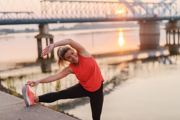 Очаровательная белокурая кавказская женщина с хвостиком и в спортивной одежде, протягивающей ногу рекой утром.