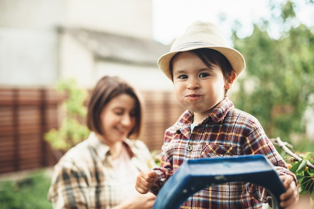 Charming caucasian boy with a hat on head eating cherries from the tree posing with his mother on background smiling