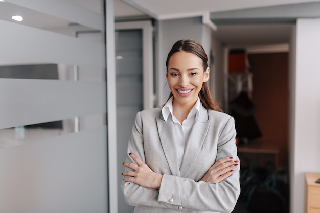 Charming caucasian businesswoman in formal wear standing in office with arms crossed. you can't discover new oceans unless you have the courage to lose sight of the shore.