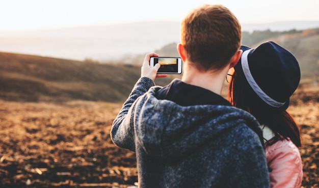 Charming caucasian couple making a selfie while posing in a field with eyeglasses and hat