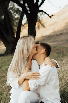 Charming caucasian couple in white clothes embracing, while woman smiling and man kissing her soft neck in the park.