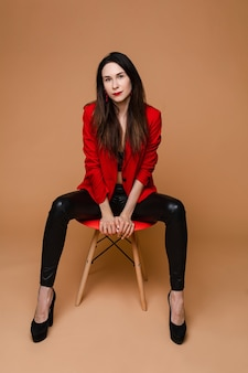 赤と黒のオフィススーツ、黒い靴が赤い椅子に座っている長く暗いストレートの髪を持つ魅力的な白人女性