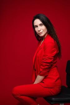 赤いオフィススーツの長い黒髪の魅力的な白人女性、黒い靴は黒い椅子に座ってカメラのポーズをとる