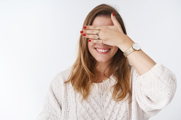 Charming caucasian girl hiding eyes behind palm smiling happily anticipating surprise playing hide-n-seek fooling around unable see close sight, standing positive joyful white background