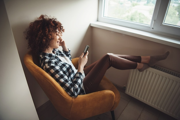 Charming caucasian girl with curly hair sitting on the armchair and smile while chatting on mobile