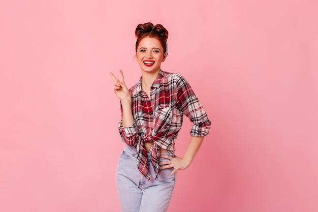 ピースサインを示す市松模様のシャツを着た魅力的な白人女性。ピンクの空間に分離された笑顔のピンナップ女性のスタジオショット。