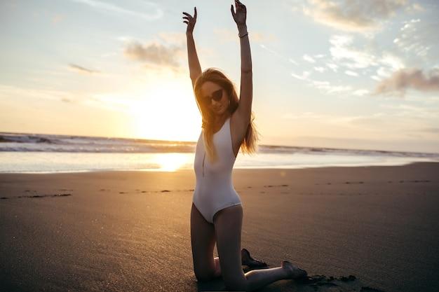Очаровательная кавказская женщина в модных серьгах позирует на песчаном пляже в отпуске.