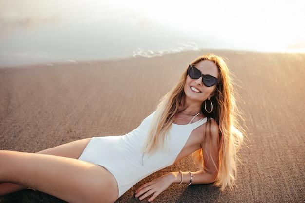 휴가에 모래 해변에서 포즈 유행 귀걸이에 매력적인 백인 여자.