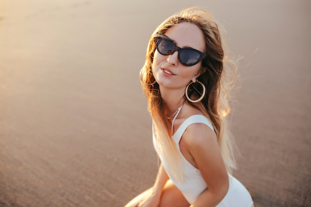 Charming caucasian woman in trendy earrings posing at sandy beach in vacation.