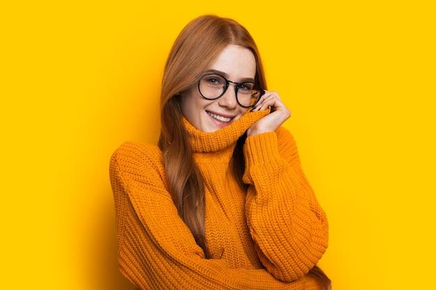 주근깨와 빨간 머리를 가진 매력적인 백인 여자는 노란색 벽에 포즈 안경과 니트 스웨터를 입고있다