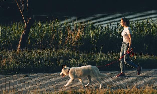 Очаровательные кавказские женщины, одетые в футболку, гуляют со своей белой собакой в парке